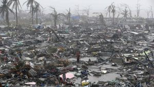 Survivors stand among debris and ruins of houses destroyed after Super Typhoon Haiyan battered Tacloban city in central Philippines November 10, 2013. Haiyan, one of the most powerful storms ever recorded killed at least 10,000 people in the central Philippines province of Leyte, a senior police official said on Sunday, with coastal towns and the regional capital devastated by huge waves. Super typhoon Haiyan destroyed about 70 to 80 percent of the area in its path as it tore through the province on Friday, said chief superintendent Elmer Soria, a regional police director. REUTERS/Erik De Castro (PHILIPPINES - Tags: DISASTER ENVIRONMENT TPX IMAGES OF THE DAY)